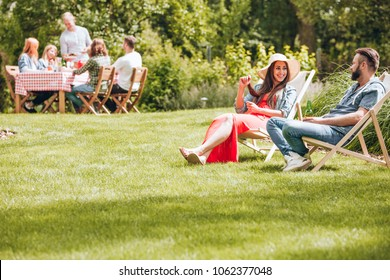 Smiling woman having fun while relaxing with a friend in the garden