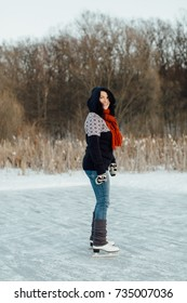 Smiling woman having a great time ice skating on a frozen lake