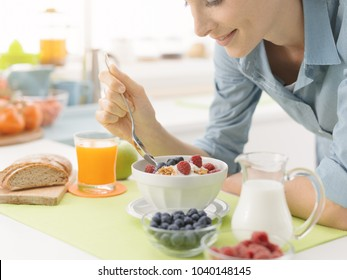 Smiling woman having an healthy delicious breakfast at home, she is eating yogurt with cereals and fresh fruit, healthy lifestyle concept