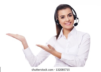Smiling woman in headset showing something