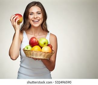 smiling woman with healthy teeth holding red and green apples in straw basket