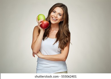 smiling woman with healthy teeth holding red and green apples. white undershirt. isolated portrait.