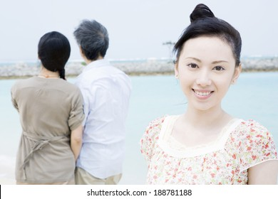 smiling woman with her back against sea