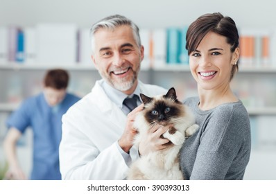 Smiling woman and her cat at the veterinary clinic, a doctor is examining the pet