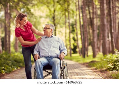 smiling woman with her disabled father in wheelchair outdoor