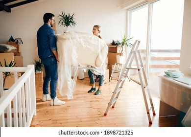 Smiling woman and her husband carrying armchair while moving into a new home.