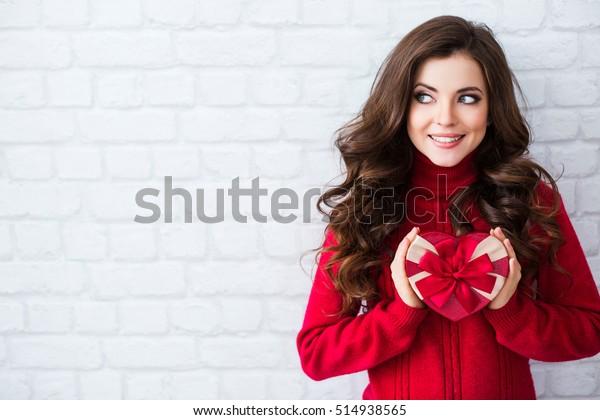 笑顔の女性が赤いギフトボックスを持つ。壁の背景。新年、クリスマス、バレンタインデーのコンセプト。