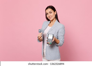 Smiling woman hold wireless modern bank payment terminal to process and acquire credit card payments isolated on pink pastel background. People sincere emotions, lifestyle concept. Mock up copy space