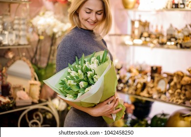Smiling woman holding a big bouquet of white tulips wrapped in a white paper on the background of flower shop