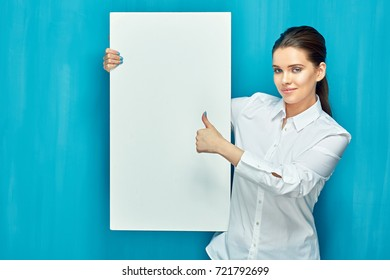 Smiling woman holding big white sign board show thumb up. Blue wall back.