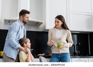 smiling woman holding bowl of vegetable salad near husband and wife in kitchen