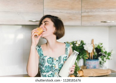 Smiling woman holding bread and milk bottle portrait on kitchen. Woman in the kitchen eating baguette. Lifestyle