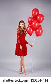 Smiling woman holding a bunch of  red balloons