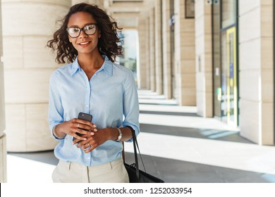 Smiling woman holding a cell phone with office building on background