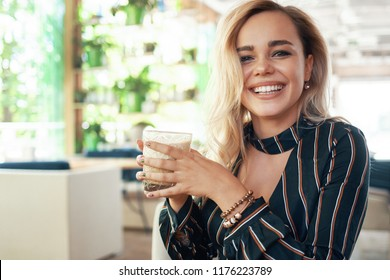 Smiling woman holding a cocktail in hands while spending her time in a modern cafe. White beautiful smile