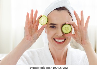 smiling woman holding cucumber slices on eyes