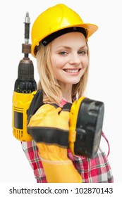 Smiling woman holding an electric screwdriver against white background