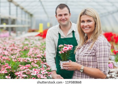 Smiling woman holding flower pot with employee in garden center