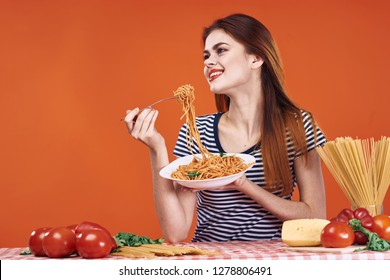 smiling woman holding a fork with a plate of spaghetti sits at the table on a red background vegetables cheese