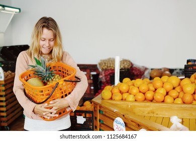 Smiling woman holding fruit basket with oranges and pineapple in shop