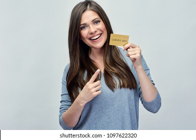 Smiling woman holding gold credit card and pointing finger. Isolated portrait girl with long hair.