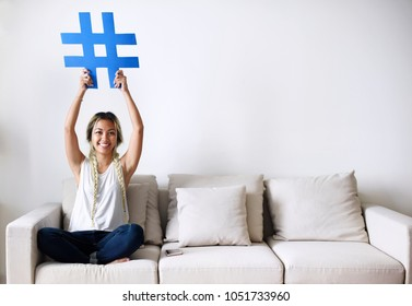 Smiling woman holding a hashtag sign social media concept