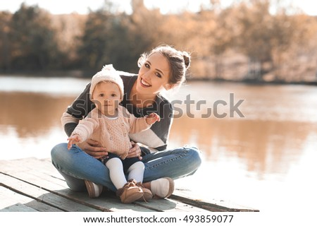 5e0dfe830 Smiling woman holding her baby girl 1 year old sitting on wooden pier in park  wearing