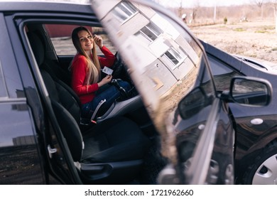 Smiling woman holding her driver license after successful driver's exam in her black car.