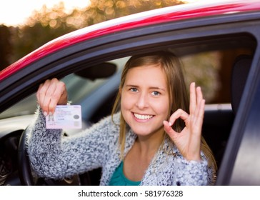 Smiling woman holding her driver license after successful driver's exam in her red car.