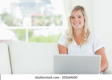 A smiling woman holding her laptop with her hands as she looks at the camera