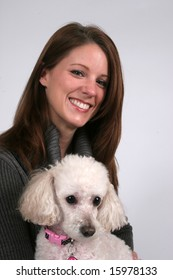 Smiling woman holding her pet poodle