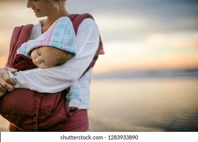 Smiling woman holding her sleeping baby at the beach.