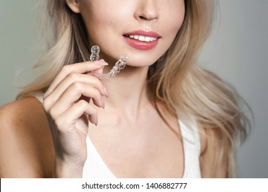 A smiling woman holding invisalign or invisible braces, orthodontic equipment. Teeth aligner for young girl. Dentistry beautiful smile concept