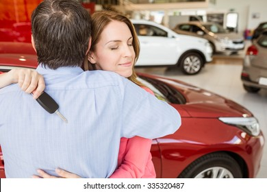 Smiling woman holding key while hugging her husband at new car showroom