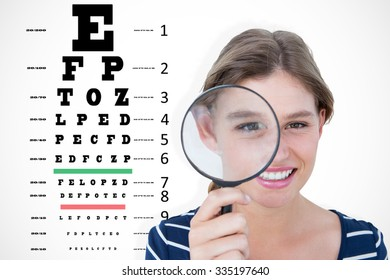Smiling woman holding magnifying glass against eye test