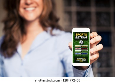 Smiling woman holding a mobile phone with sports betting website in the screen.