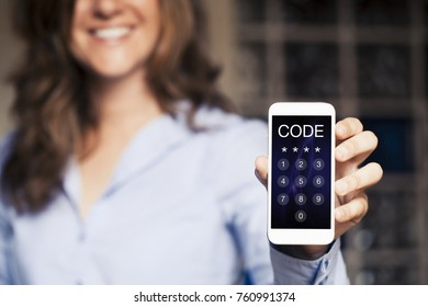 Smiling woman holding a mobile phone with passcode in the screen. Unlocking device.
