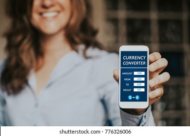 Smiling woman holding a mobile phone with currency converter app in the screen.