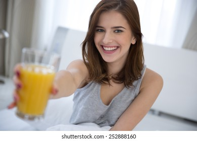 Smiling woman holding orange juice on the bed