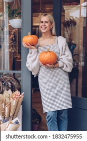 Smiling woman is holding pumpkins in front of her shop