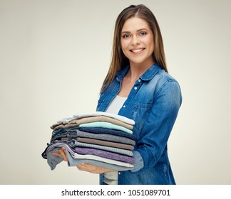 Smiling woman holding stack of folded wool clothes. Isolated housekeeper portrait on white.