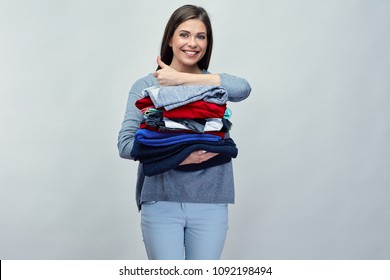 Smiling woman holding stack of folded clothes showing thumb up. Isolated studio portrait.