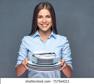 Smiling woman holding stack of plate with knife and fork. Studio isolated portrait.