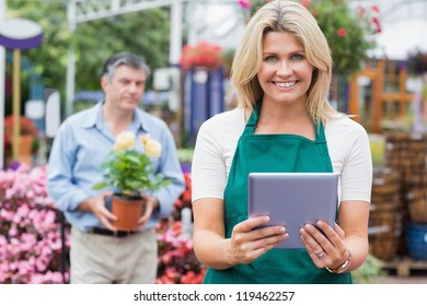 Smiling woman holding a tablet pc with customer holding plant behind her in garden center