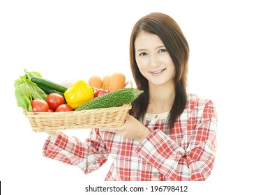 Smiling woman holding vegetables