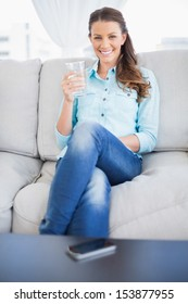 Smiling woman holding water glass sitting on sofa in bright living room