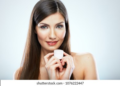 Smiling woman holding white container with skin care cream. Isolated portrait on white.