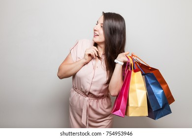 Smiling woman holds bags from clothing stores