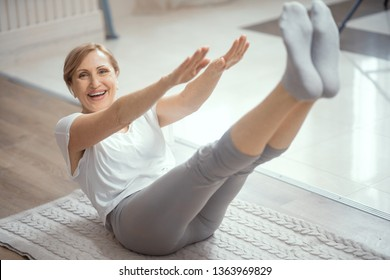 Smiling Woman Holds Her Arms And Legs In The Air Balancing On Her Back. Mature Woman Does Yoga Exercises On A Mat. Fitness Concept