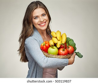 smiling woman holds straw basket with healthy food, bananas, apple, tomato, broccoli vegetables and fruits.